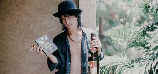 Izzy Stradlin Guns N' Roses holding shield for ML popularity vote and sake at a hotel, unknown, 1988. (Photo by Koh Hasebe/Shinko Music/Getty Images)